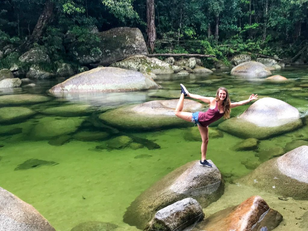 woman-doing-yoga-post-standing-on-rock-in-rainforest