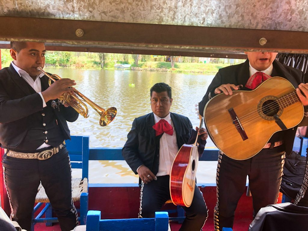 three mexican mariachi men playing on xochimilco river boat