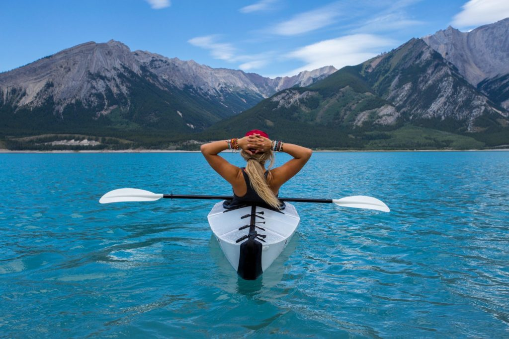 solo female traveler kayaking blue lake