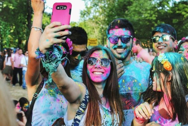 friends taking a selfie covered in colorful powder
