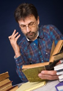 Mature man reading old book surrounded by heaps of books