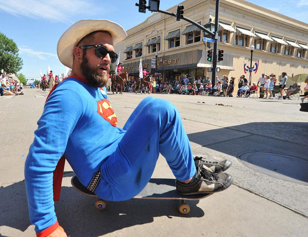Brady McLean rolls around dressed as superman during the 2014 Sheridan WYO Rodeo Parade Friday morning on Main Street.