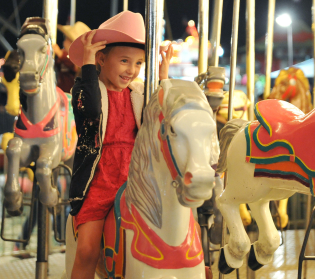 Six-year-old Lyliauna Smith gets ready for the ride to begin Saturday night at the carnival during the Sheridan WYO Rodeo at the Sheridan County Fairgrounds arena.
