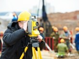 a man with yellow construction hat looking through a Surveyor theodolite on tripod