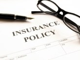 insurance policy and black pen and glasses on top