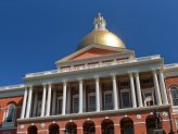 The state house brick building with gold dome on top of it.