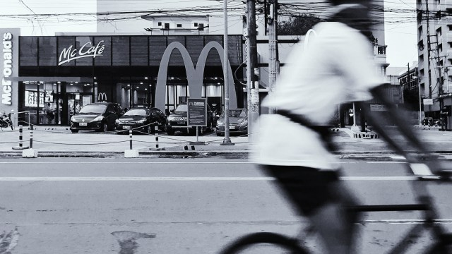 Street Photography in Manila, Philippines - Man in Bike Passing by McDonalds