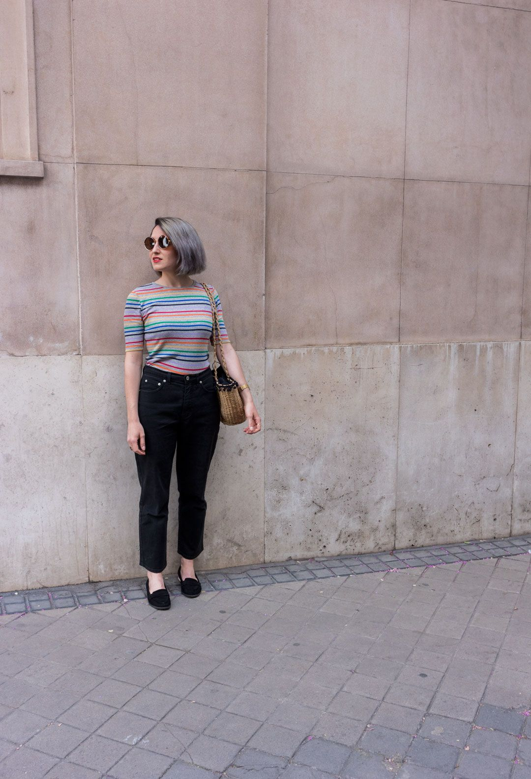She talks Glam | Rainbow tee, black mom jeans and woven straw bag with black pom pomps | Casual chic outfit | Madrid streetstyle