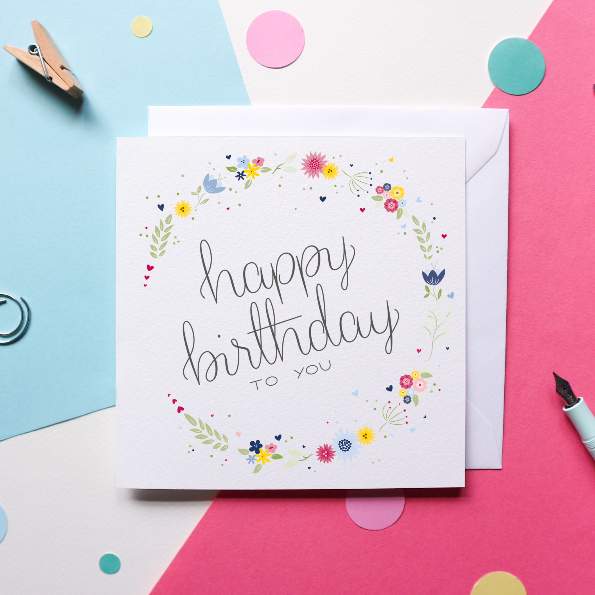 "A charming Birthday card that reads ""Happy Birthday to you"" in hand drawn lettering in grey text against a white background, surrounded by a circle of bright flowers in pinks, blues and yellows. The card sits against a white envelope and a blue and pink background with bright confetti, a pen and some paper clips."