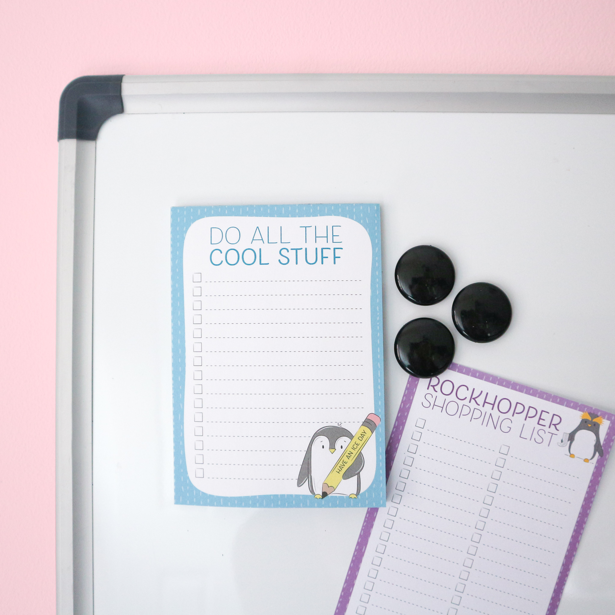 """Do All the Cool Things"" To-Do List Notepad with an illustration of a penguin holding a pencil that reads ""Have an ice day"" This image shows the magnetic option on a magnetic notice board with some magnets and other to-list pages."