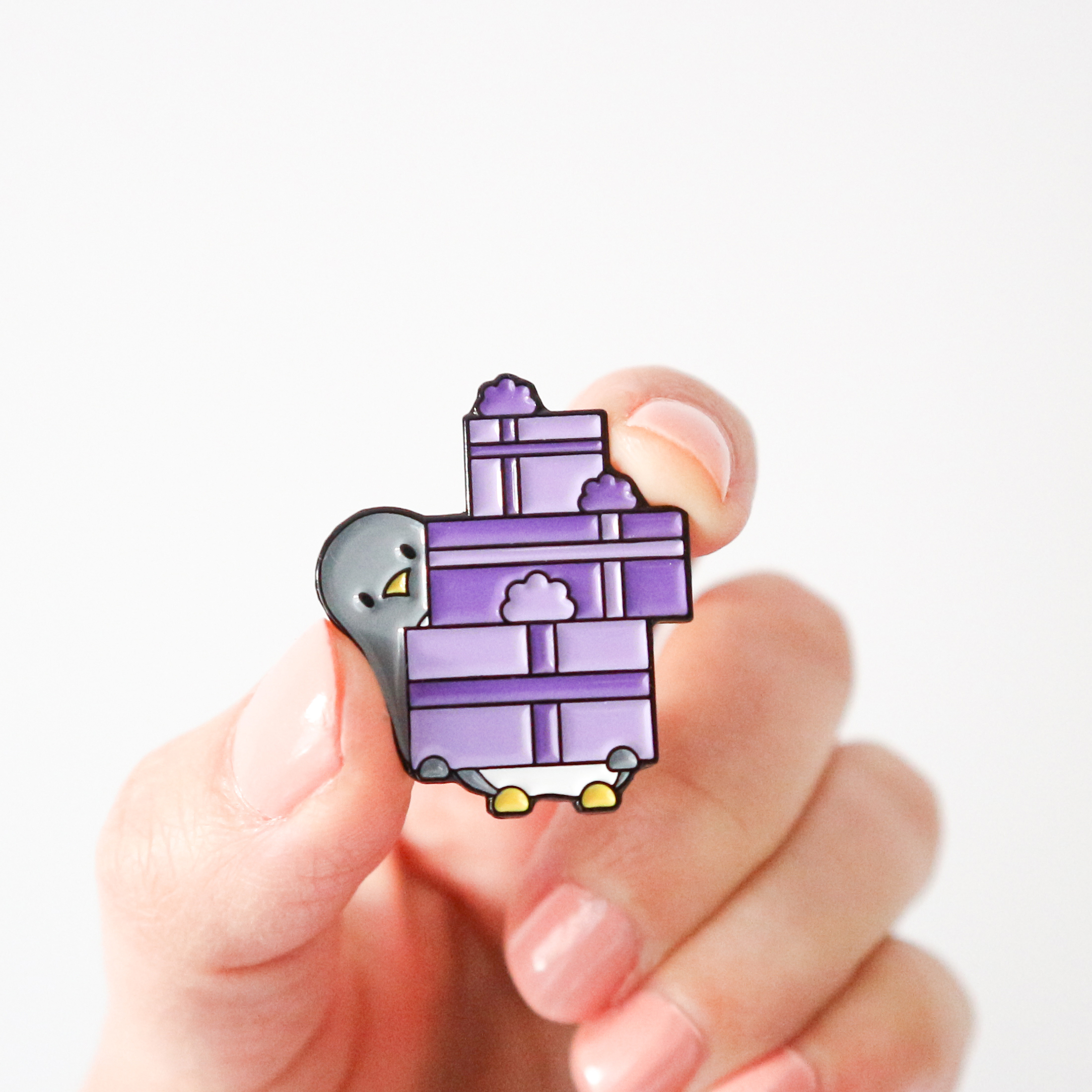 an illustrated enamel pin design of a cute penguin with a big stack of purple gifts, perfect for a birthday. The pin is being held by a hand against a white background.
