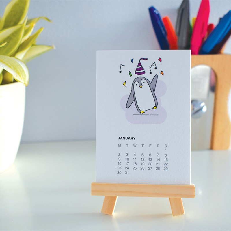 January page of 2017 penguin calendar sitting on a miniature easel, styled in front of a plant and pencil pot.