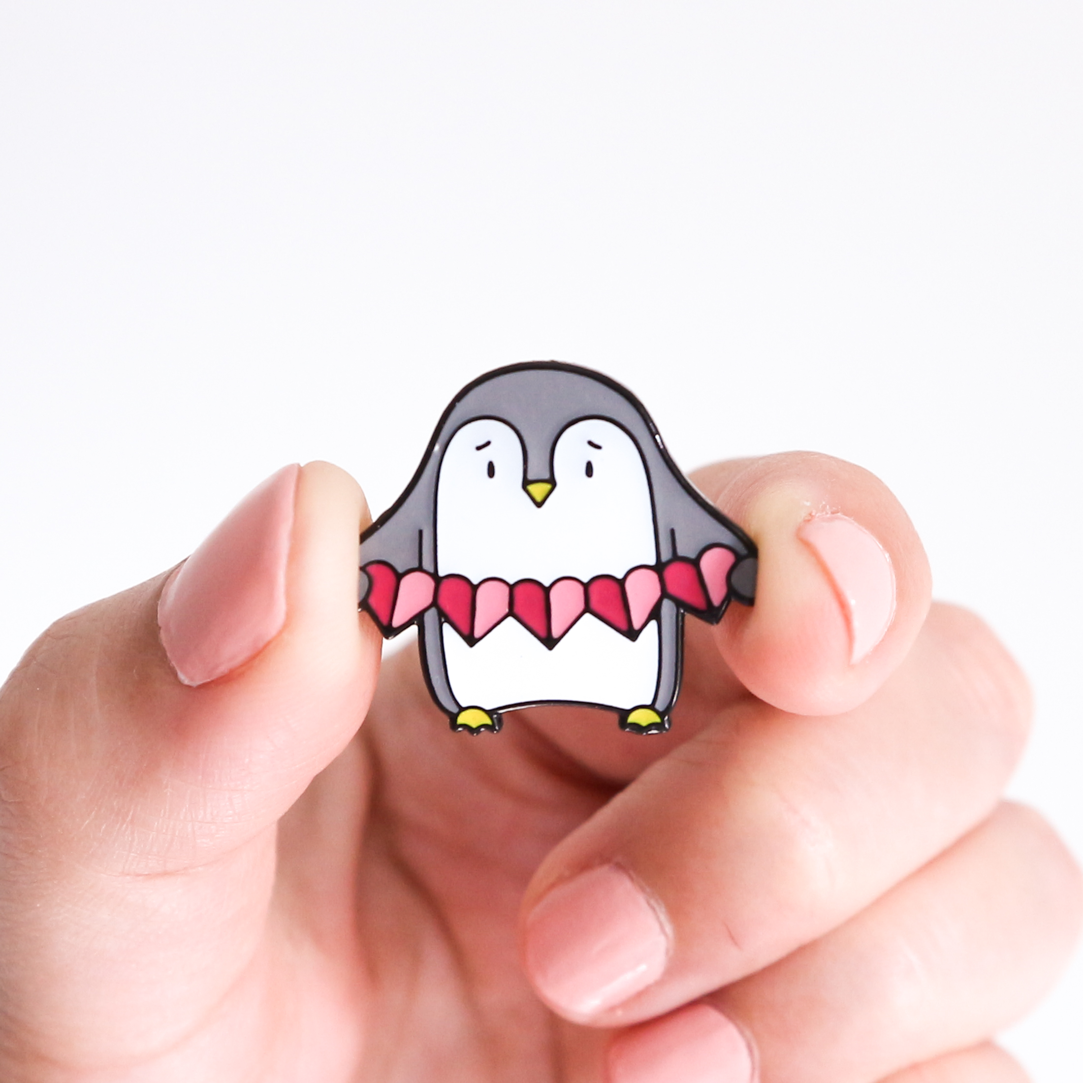 Photo of a hand holding a penguin enamel pin. The pin design shows a cute penguin holding a pink heart garland.