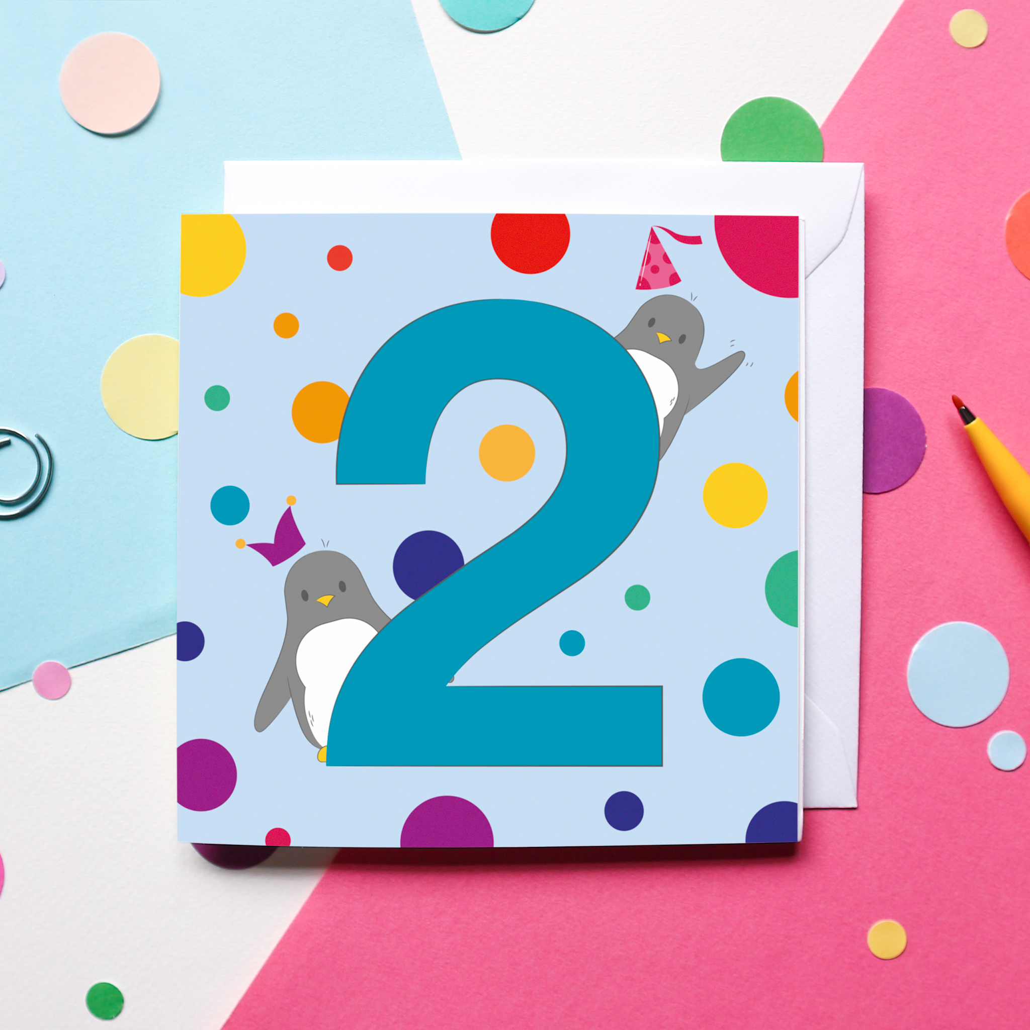 A Penguin-themed 2nd Birthday Card on a colourful background surrounded by confetti and a pen.
