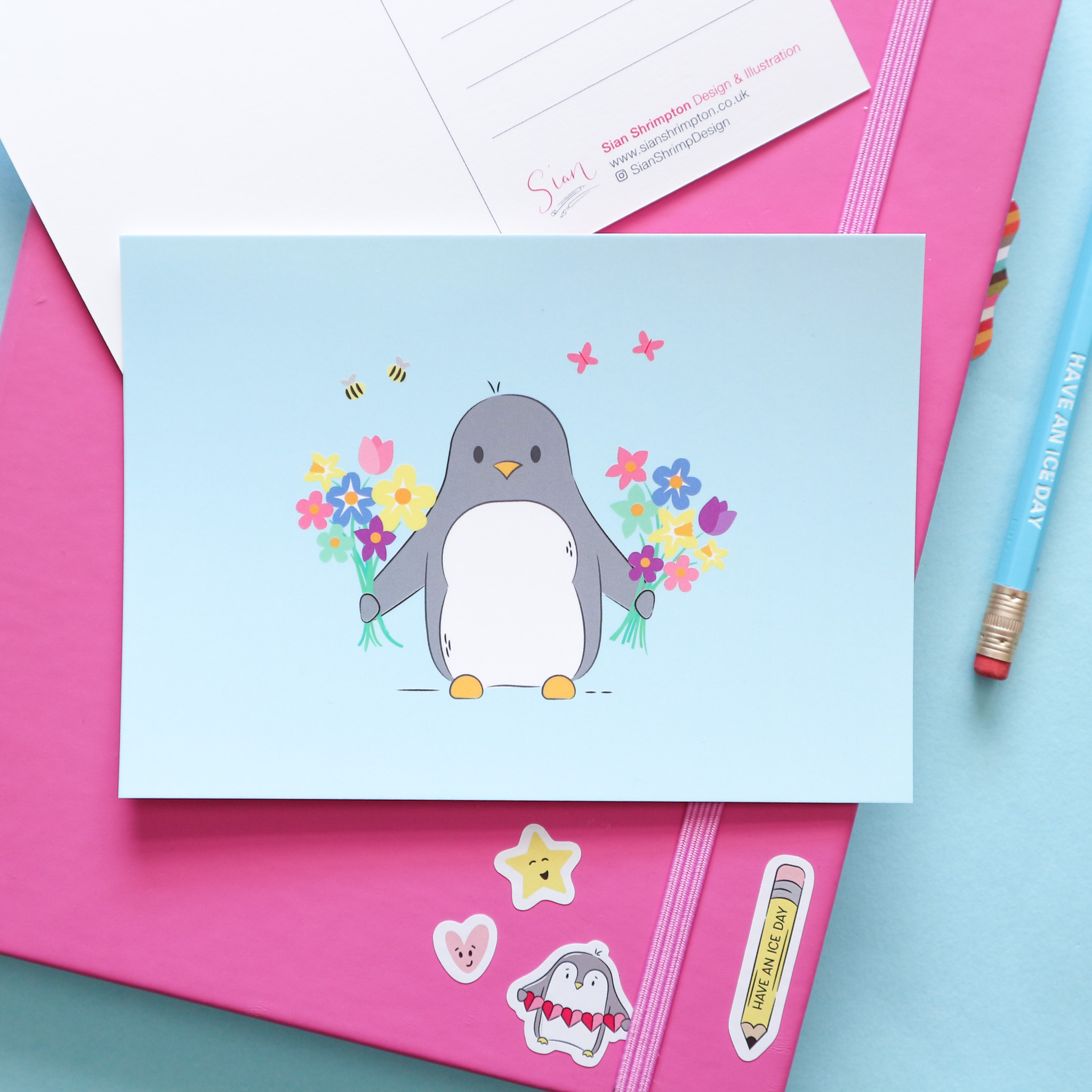 A postcard design showing a penguin holding two bunches of flowers. Styled with a pink notebook and a pencil on a blue background.