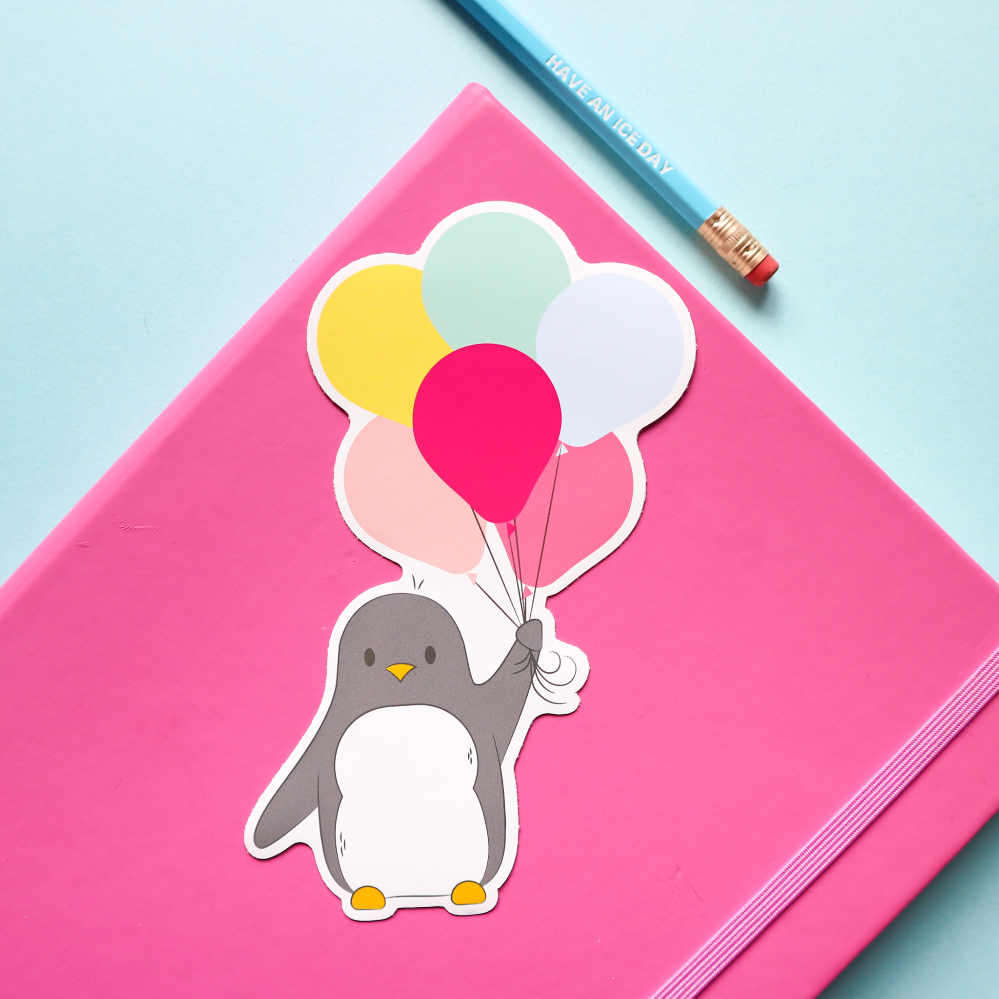 sticker design of Penguin holding a big bunch of colourful balloons. The balloons are pale pink, yellow, mint green, pale blue, bright pink and mid pink. Styled against a background of a pink notebook and a blue pencil, all against a pale blue background.