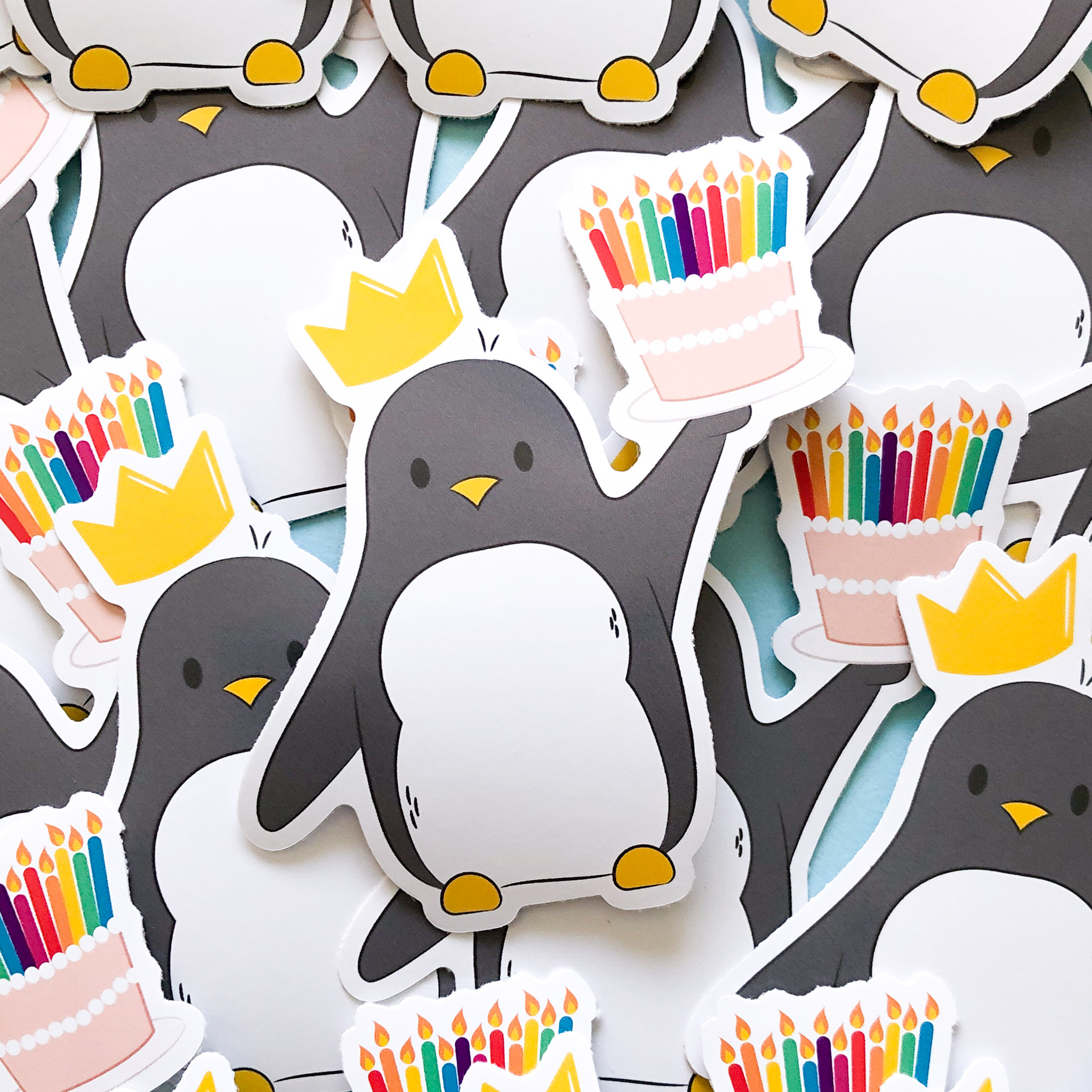 Multiple stickers all layered on top of each other, this sticker design of penguin holding a birthday cake with lit, colourful candles on top and he's wearing a yellow birthday crown.