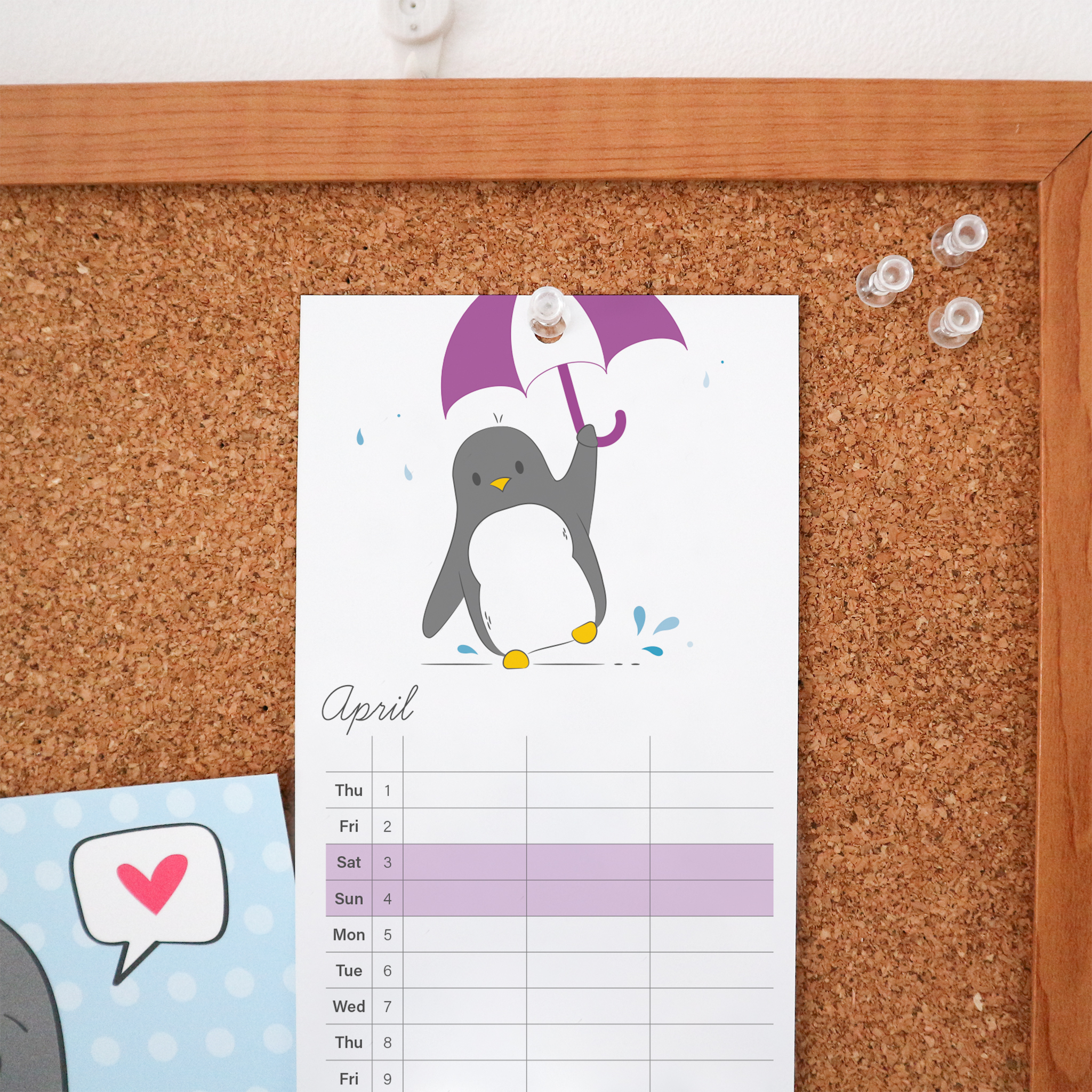 The April page of the 2021 Calendar is an illustration of penguin jumping around in some puddles with a purple and white umbrella. This Calendar is a wire bound tall calendar and is styled against a cork board background.