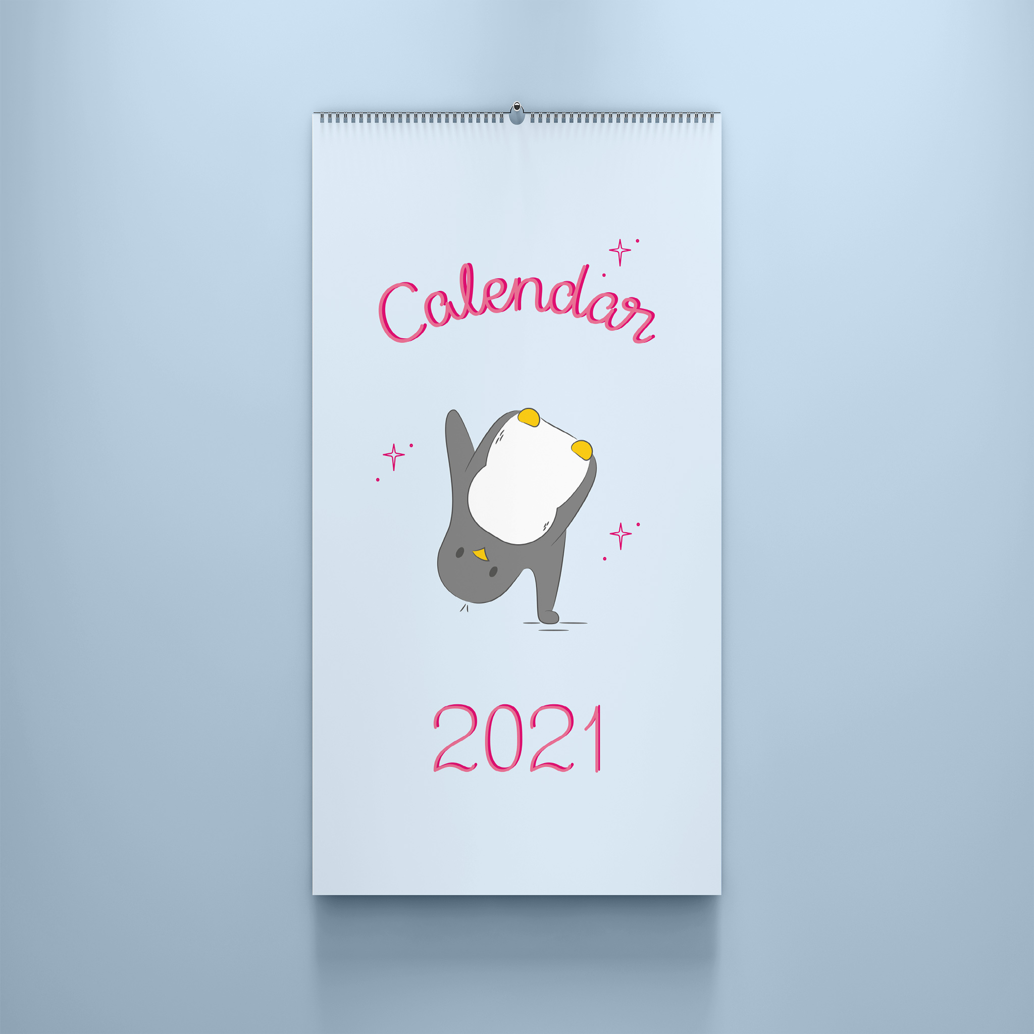 The front page of the 2021 calendar is an illustration of penguin cartwheeling, it has a pale blue background and the words calendar 2021 are hand-lettered in pink. This Calendar is wire bound A4 and is styled against a blue background.