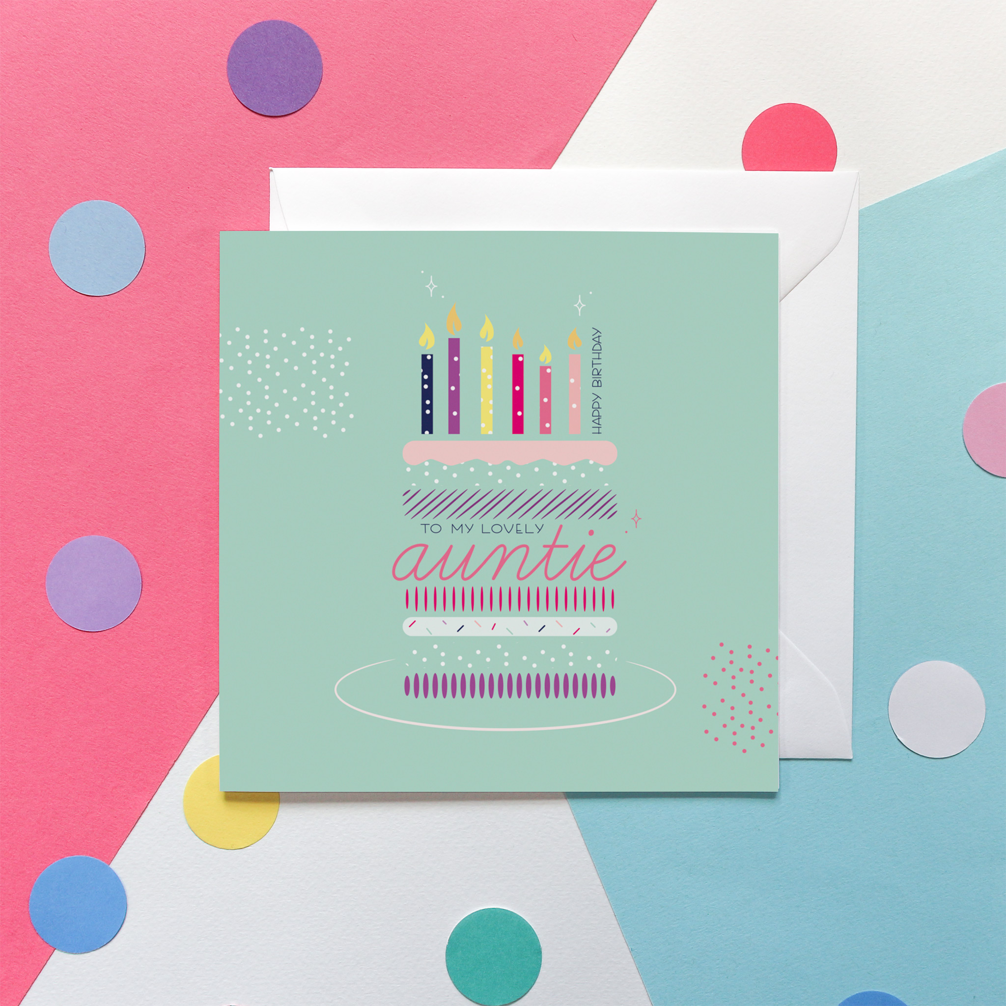 """Photo of a Birthday Card. The design shows a stylised colourful birthday cake with the words """"Happy Birthday...to my lovely Auntie"""" and seven birthday candles. The background of the card is navy blue and the design is in pinks, purples, mint green and yellows. It is set against a pink, white and blue background and colourful confetti."""