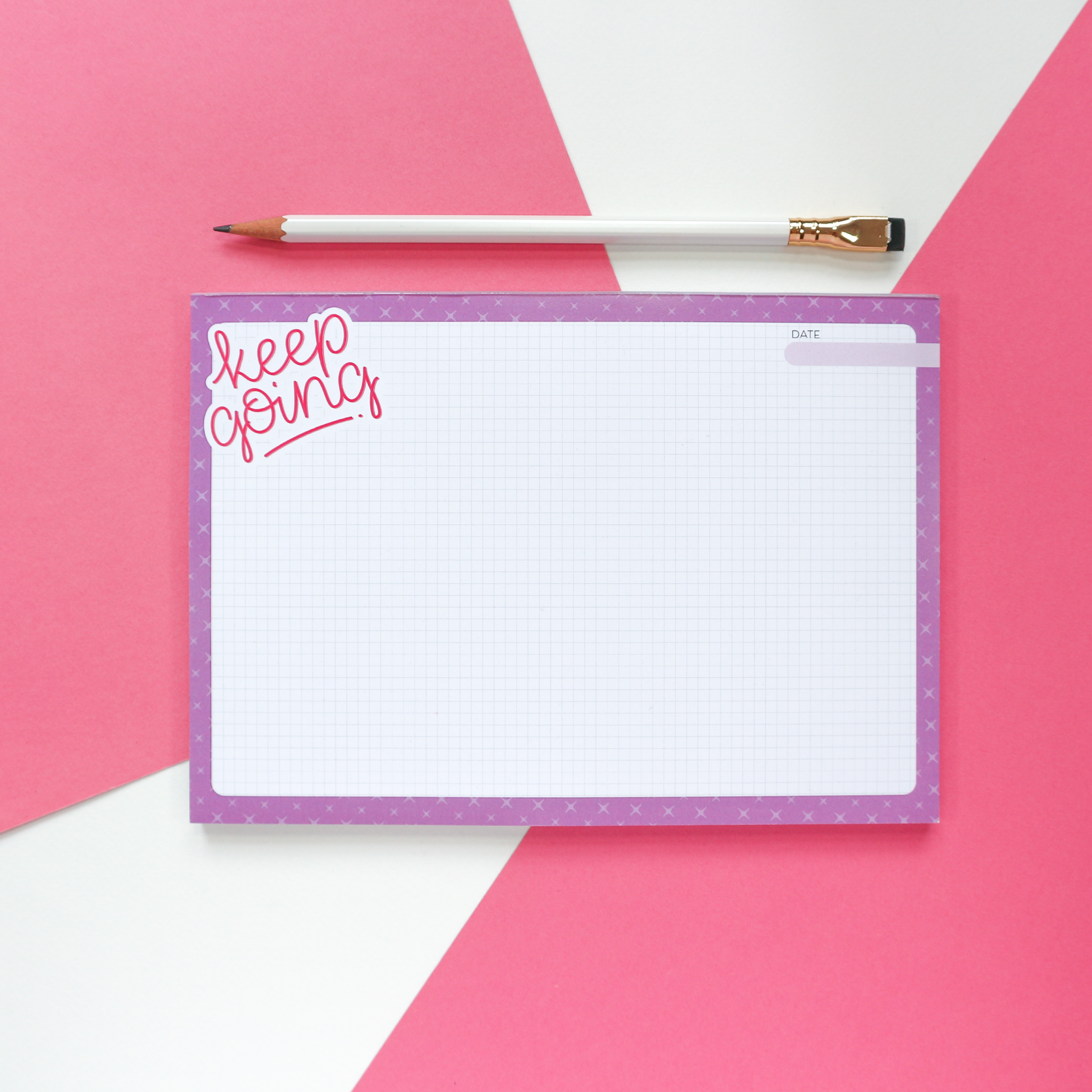 """A photo of an A5 deskpad, which has a purple border, grid paper and reads """"keep going"""" in pink hand drawn lettering in the top corner. Deskpad sits against a pink and white background styled with a white pencil."""