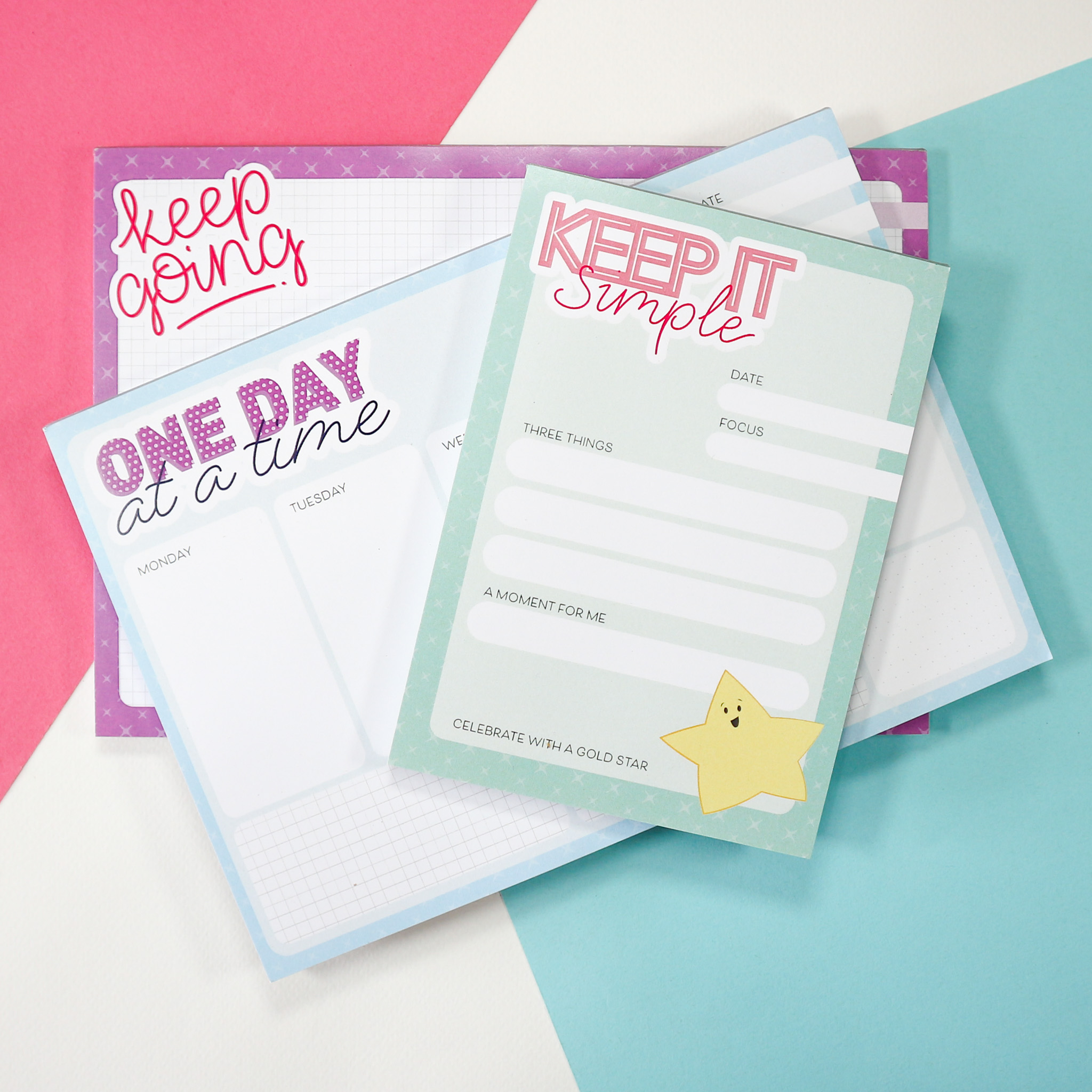 """A photo of a purple jotter pad that reads """"keep going,"""" a weekly planner pad that says """"one day at a time"""" and a to-do list notepad that reads """"keep it simple"""""""