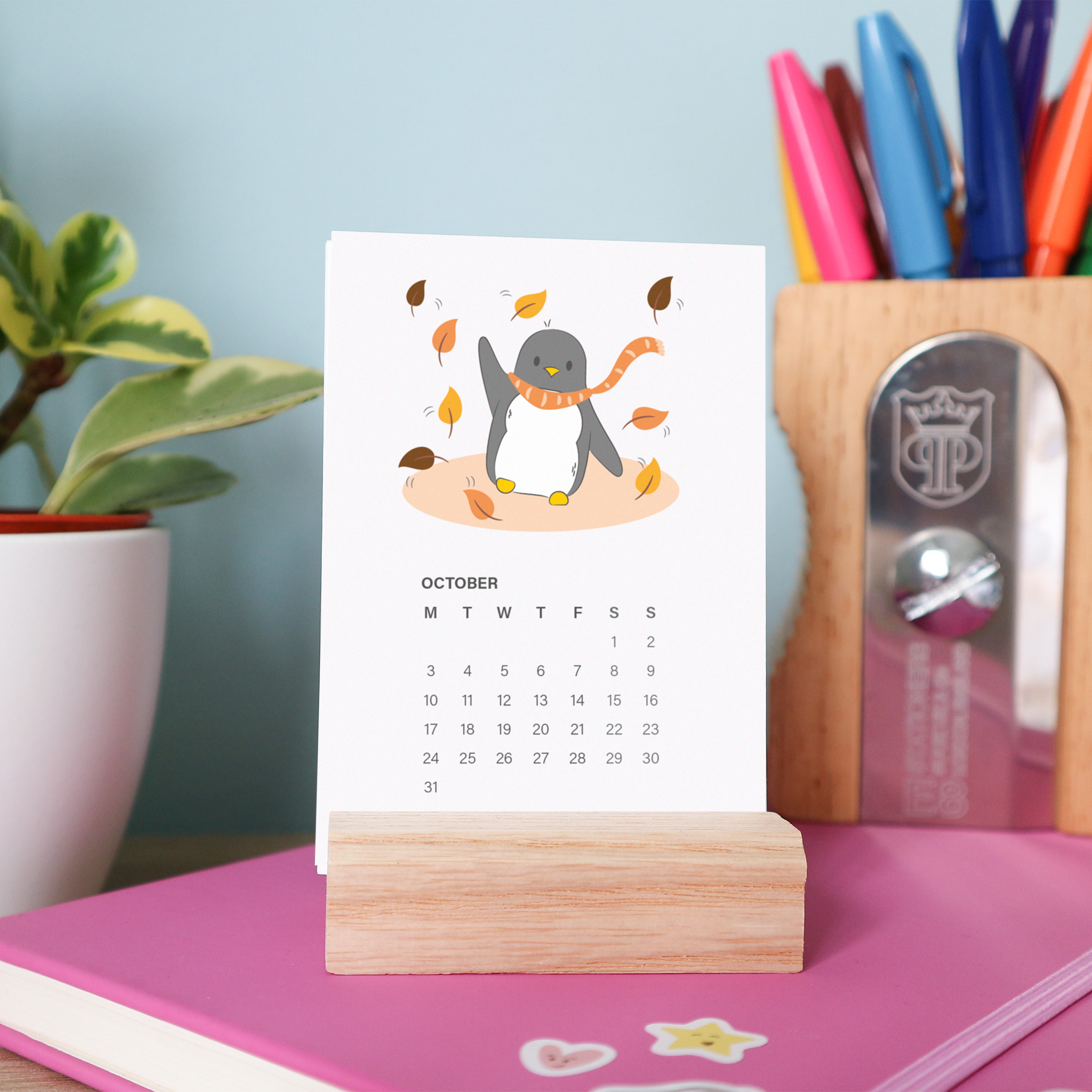 A photo of the October page of the 2022 Penguin Calendar. The page shows Penguin dancing in the orange leaves of autumn wearing an orange scarf. The calendar is sitting on a wooden stand. In the background is a colourful pencil pot and a plant.