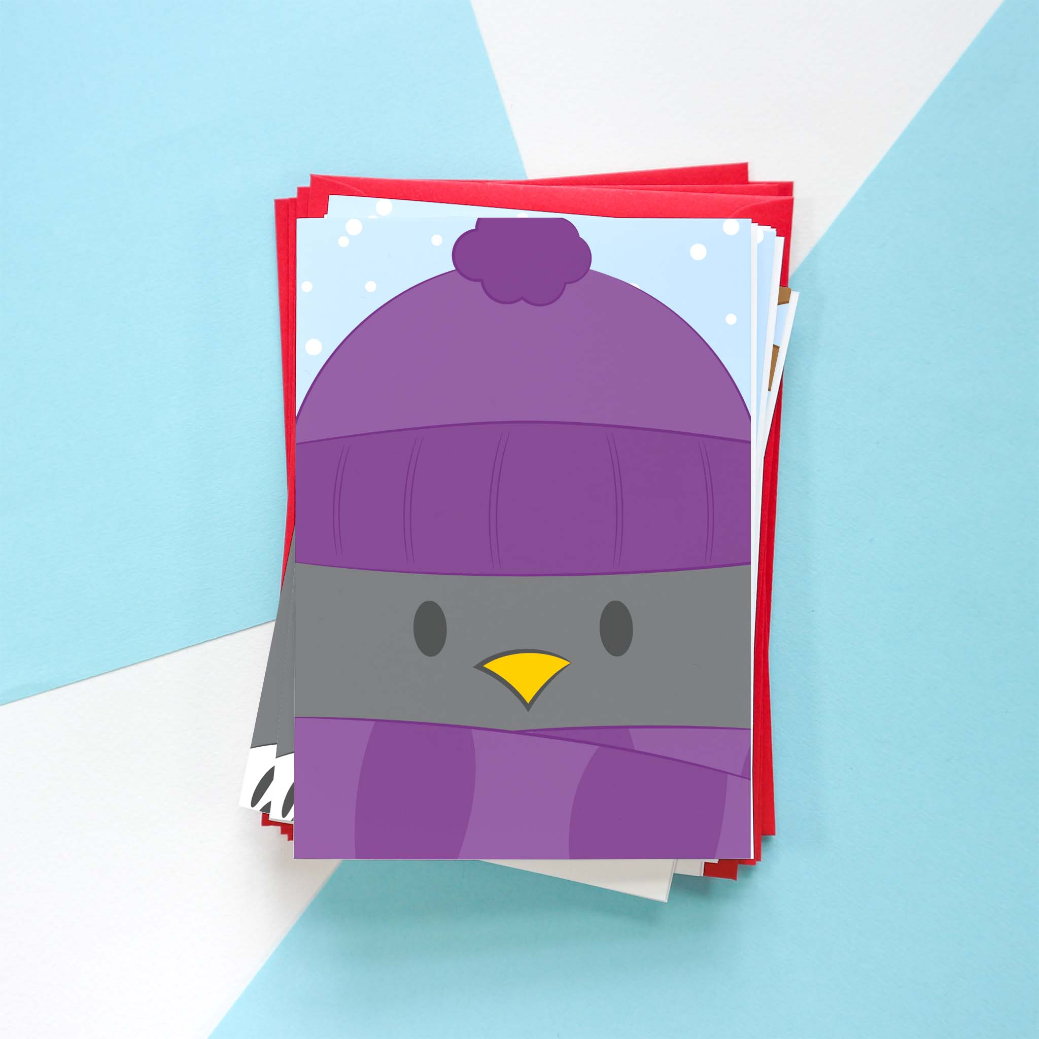 A photo of a Penguin Christmas card design. This design is of Penguin dressed up for winter in a purple hat and scarf.