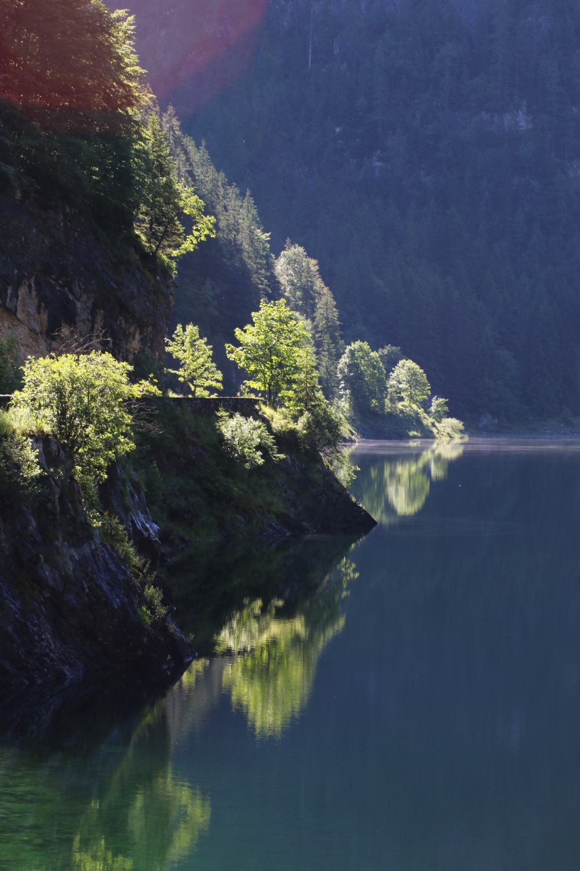 The sun catching the trees and casting great reflections on Lake Gosau