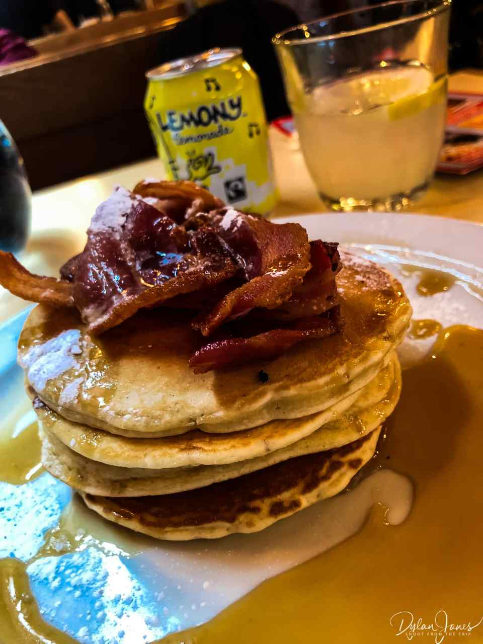 Pancake stack with bacon and maple syrup.