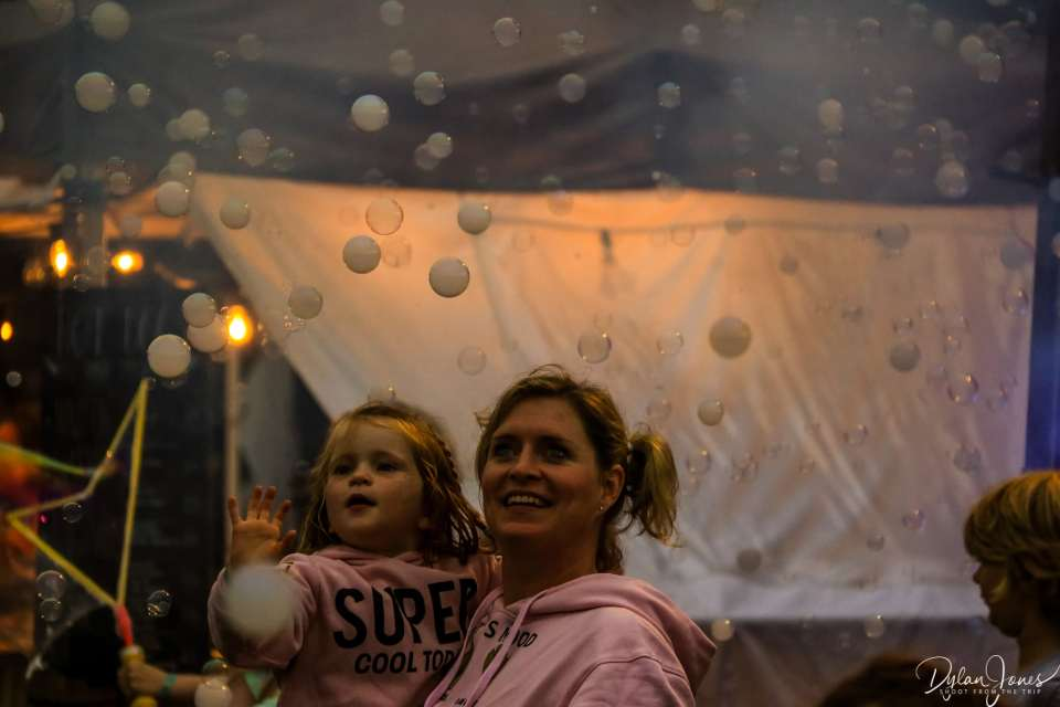 A young girl trying to catch bubbles at Deer Shed Festival