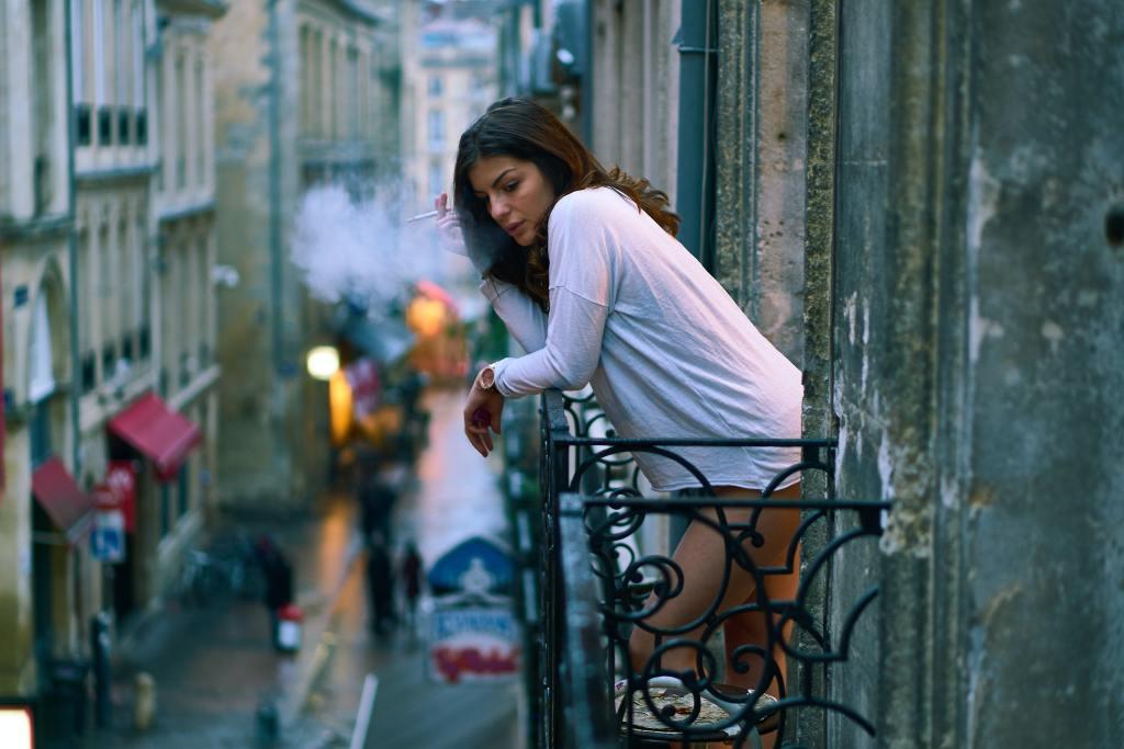 Woman on a balcony in Bordeaux France