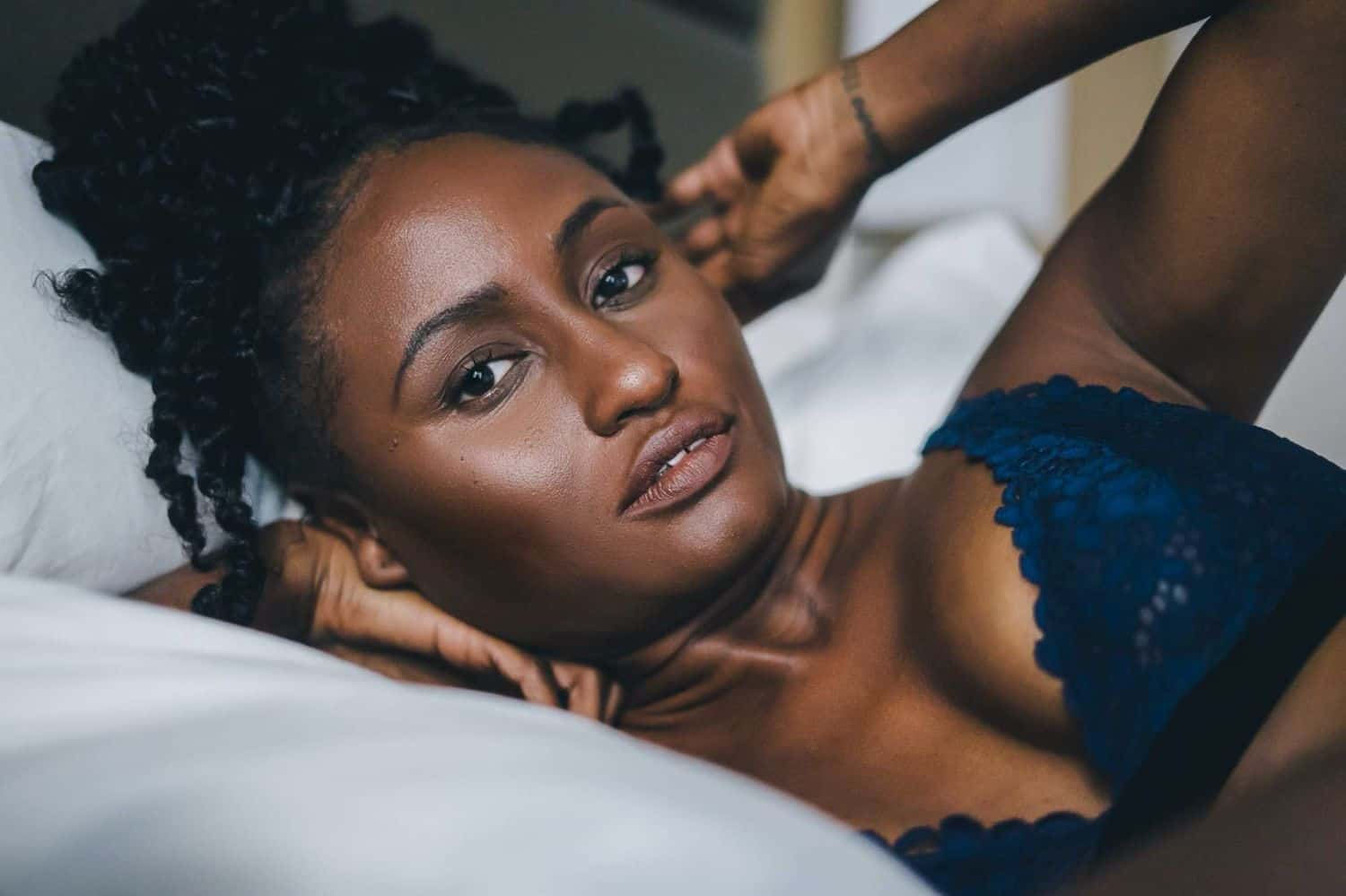 A Black model in blue lingerie poses for photographer Toni Black during a boudoir session on a white bed