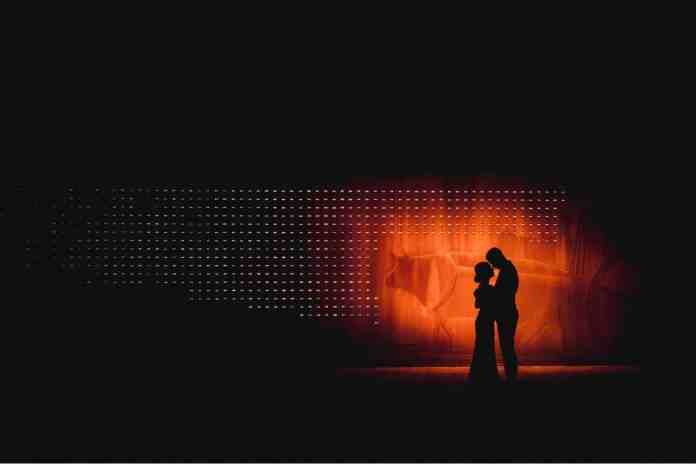 A couple is silhouetted against a glowing orange background. The photograph is framed so that the couple is highlighted on the right side of the image, with dark night all around their glowing forms. Black & Gold Photography educates photographers on how to make wedding portraits using off-camera flash.