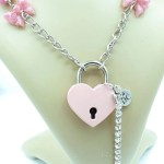Closeup detail of pink heart shaped padlock with key attached by rhinestone chain.