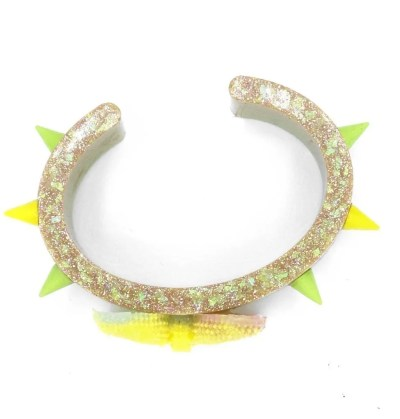 Top view of glitter infused resin cuff with yellow and green spikes and bow in center