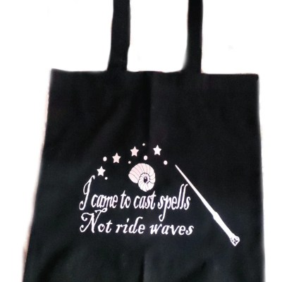 """Black beach tote bag with words """"I came to cast spells, not ride waves"""""""
