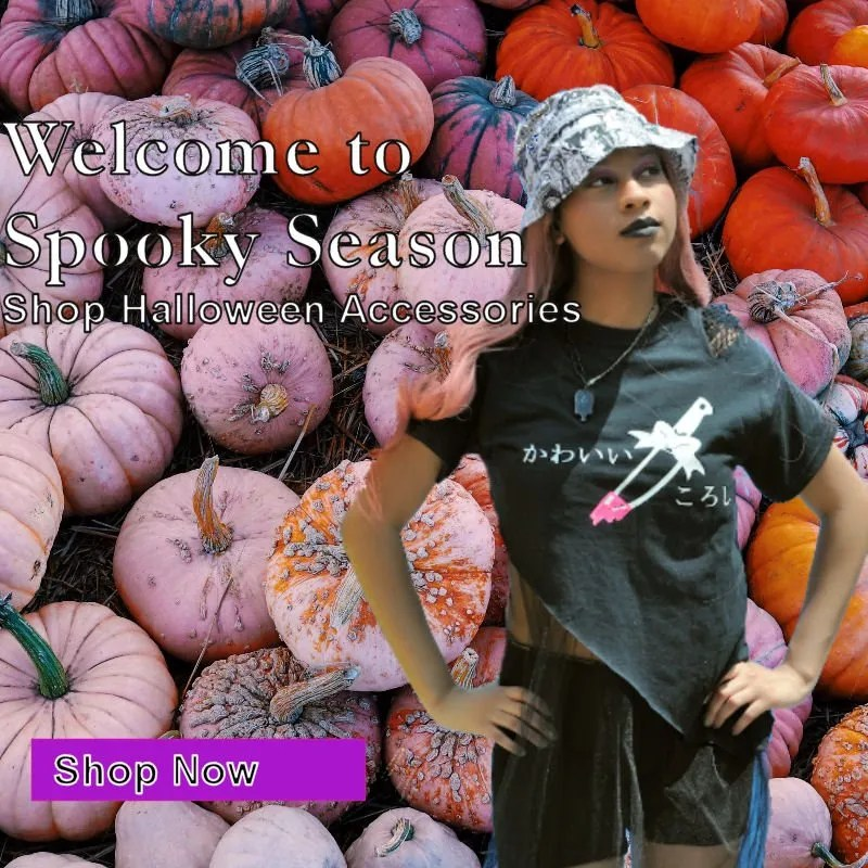 Woman in screen printed goth style t-shirt stands in front of colorful pumpkins
