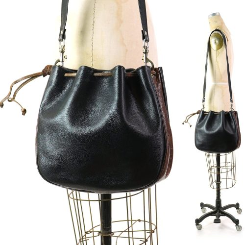 Vintage 80s Drawstring Leather Crossbody Bucket Bag. Black leather with brown leather trim. Fully lined. One zippered pocket inside.
