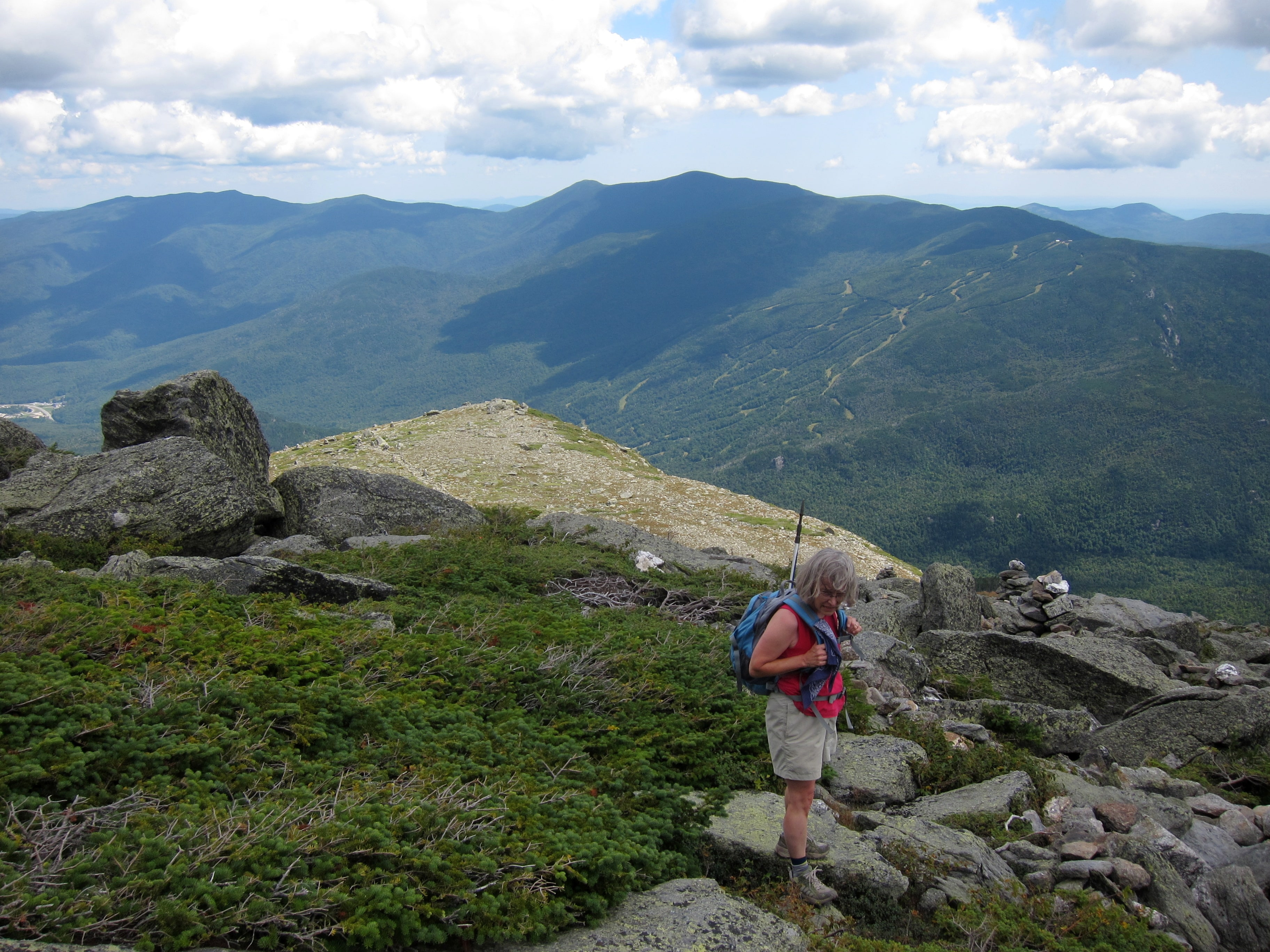 A hiker on Boott Spur, Mount Washington. Wildcat ski area in the background.