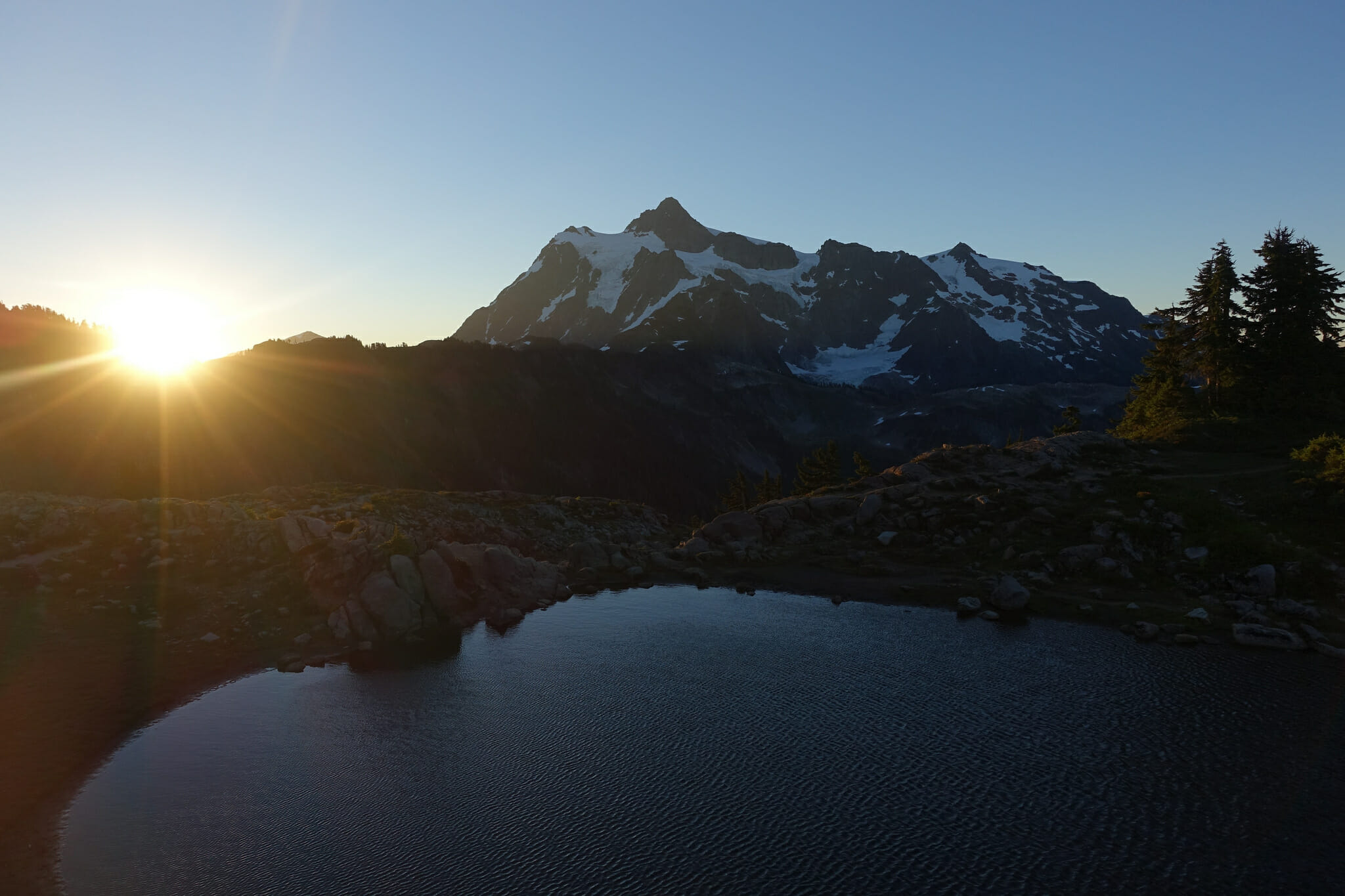 The sun rises over Mount Shuksan and a tarn