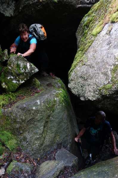 Two hikers emerge from between boulders on the Subway Loop of King Ravine