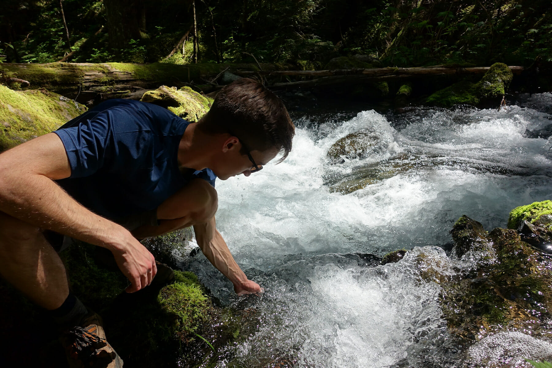 Kyle dips his hand in the Upper Big Quilcene
