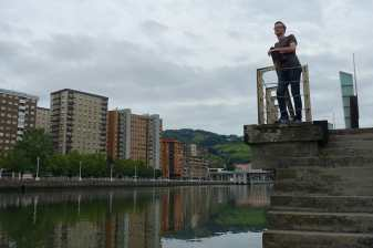 Kyle stands near the river in Bilbao
