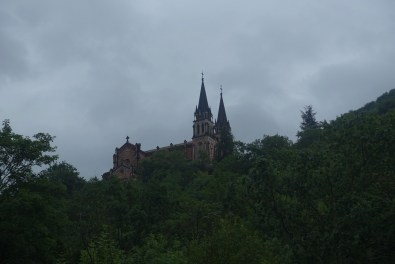 The pink church of Basilica of Santa María la Real de Covadonga, seen through trees on a cloudy day