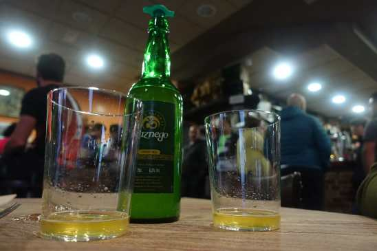 A bottle and two glasses of cider on a wooden table in a bar.