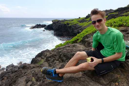 Kyle eating an apple along the coast near Kuloa Point