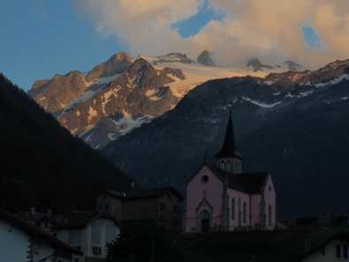 Pink church and alpenglow on the mountains, view from Auberge Mont Blanc