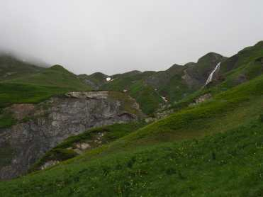 Waterfall, green slopes, and grey cliffs
