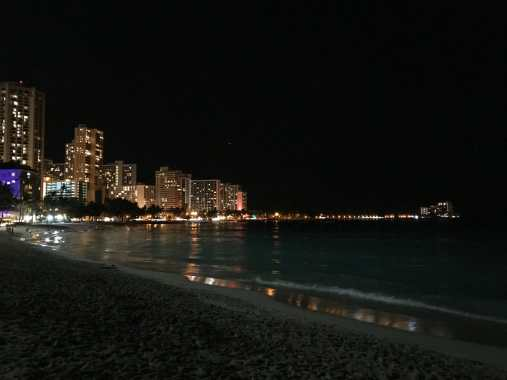 Beach and buildings of Waikīkī at night